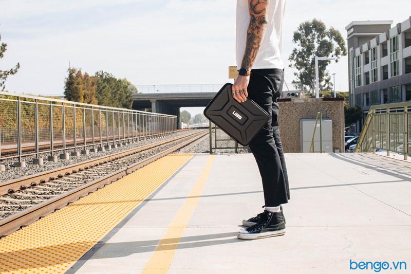Người mẫu đang cầm túi bảo vệ laptop UAG